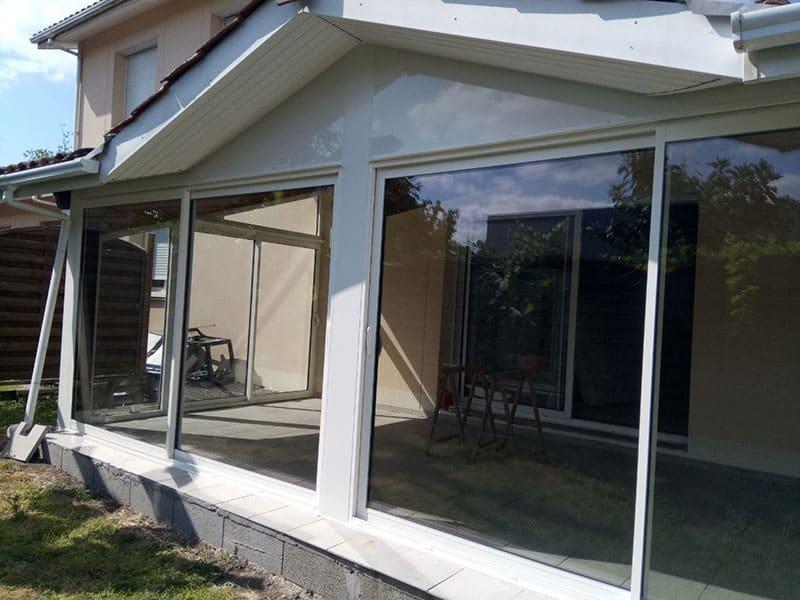 Terrasse transformée en véranda, avec des la pose de baies vitrées en alu blanc